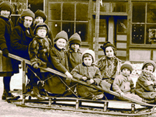 Children on an antique wood sleigh